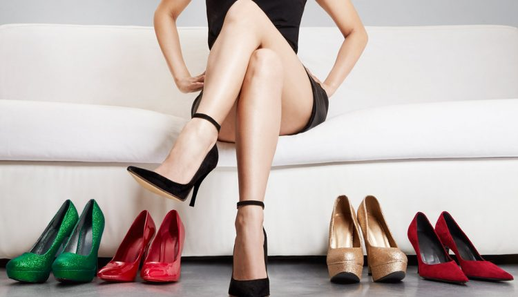 Beautiful legs woman crossing legs on the sofa with many shoes.
